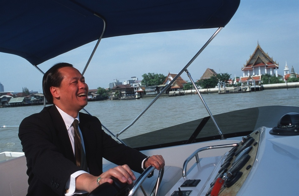Banthoon Lamsam, Thai Farmers Bank Plc President and Chairman of the Thai Bankers Association, drives his bank's motor cruiser boat on his way to a meeting with the Governor of the Bank of Thailand. Banthoon Lamsam has been credited with turning around the fortunes of his Thai Farmers Bank after the economic crash of 1978. US-educated (Harvard MBA), his management style is considered iconoclastic by traditional Thai business standards, but is paying off. His is the only bank likely to make a profit in 2000.