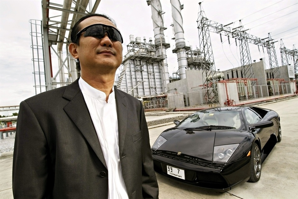 Vikrom Kromadit, CEO of Amata Corp., posing against a backdrop of the power supply plant for the massive Amata Nakorn Industrial Estate.