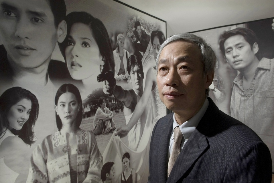 Paiboon Damrongchaitham, Founder and Chairman of one of Thailand's largest music industry companies, Grammy Entertainment poses for a portrait in front of a photo-mural of Grammy actors and actresses who have starred in various films and television dramas and soap operas.